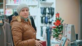 La mujer atractiva compra ropa, sostiene el dinero a disposición, oficina de los cajeros Centro comercial almacen de video