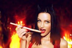 La mujer atractiva con los labios rojos prueba la comida en infierno fotos de archivo libres de regalías