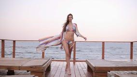 La mujer atractiva, confiada, de moda en bikini y la túnica camina con área de madera del salón cerca del mar Front View metrajes