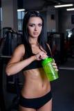 La mujer atractiva de la aptitud en la ropa de deportes que descansa después de pesas de gimnasia ejercita en gimnasio Muchacha h fotos de archivo
