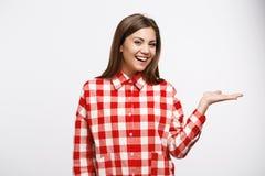 La mujer atractiva de la castaña en camisa roja y blanca mira derecho Foto de archivo libre de regalías