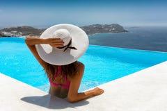 La mujer atractiva del viajero se relaja en una piscina imagenes de archivo