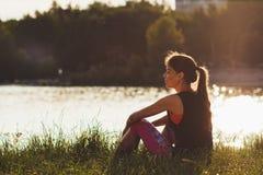 La mujer atractiva deportiva en los lagos costea en la puesta del sol Imágenes de archivo libres de regalías