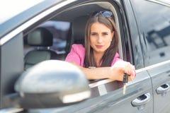La mujer atractiva distribuye el coche de la ventana que lleva a cabo llave del coche Fotos de archivo libres de regalías
