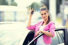 La mujer atractiva distribuye el coche de la ventana que lleva a cabo llave del coche Fotos de archivo