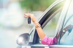 La mujer atractiva distribuye el coche de la ventana que lleva a cabo llave del coche Foto de archivo libre de regalías