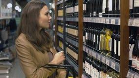 La mujer atractiva elige la botella de vino en el supermercado