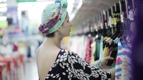 La mujer atractiva elige la ropa del bebé en supermercado almacen de video