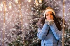 La mujer atractiva en abajo chaqueta azul sopla los copos de nieve en una nieve Imagenes de archivo