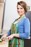 La mujer atractiva en delantal rayado taja verduras foto de archivo