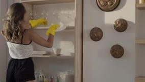 La mujer atractiva en guantes de goma amarillos quita baile de fin de curso del polvo el estante en la cámara lenta, mujer joven  almacen de metraje de vídeo