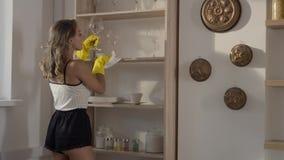 La mujer atractiva en guantes de goma amarillos quita baile de fin de curso del polvo el estante en la cámara lenta, mujer joven  metrajes