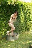La mujer atractiva en jardín toma una ducha fría Foto de archivo