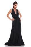 La mujer atractiva en un vestido largo negro está mirando lejos Fotos de archivo libres de regalías