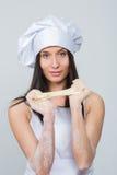 La mujer atractiva en uniforme del cocinero amasa la pasta imagen de archivo libre de regalías