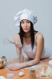 La mujer atractiva en uniforme del cocinero amasa la pasta fotografía de archivo
