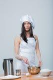 La mujer atractiva en uniforme del cocinero amasa la pasta imágenes de archivo libres de regalías
