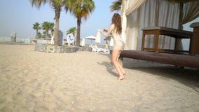 La mujer atractiva está caminando en la playa almacen de video