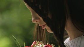 La mujer atractiva está oliendo el ramo de flores y después está mirando para arriba y está disfrutando de la naturaleza Retrato  almacen de metraje de vídeo