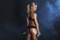 La mujer atractiva fuerte está entrenando con los barbells Fotos de archivo libres de regalías