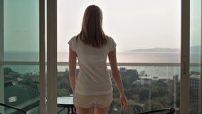La mujer atractiva hermosa abre resbalar-puertas en el balcón Va afuera y se sienta en una silla la relajación almacen de video