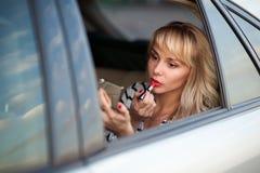 La mujer atractiva hermosa se atusa en el coche foto de archivo libre de regalías