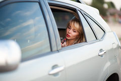 La mujer atractiva hermosa se atusa en el coche imagen de archivo