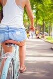 La mujer atractiva hermosa se vistió en pantalones cortos viaja en bicicleta Imagen de archivo