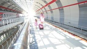 La mujer atractiva joven con la maleta y su hija bonita en el ferrocarril van al tren metrajes