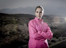 La mujer atractiva joven del deporte en la chaqueta corriente que presenta con la actitud desafiante se refresca Imagen de archivo libre de regalías