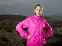 La mujer atractiva joven del deporte en la chaqueta corriente que presenta con la actitud desafiante se refresca Fotos de archivo