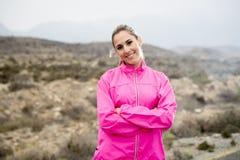 La mujer atractiva joven del deporte en la chaqueta corriente que presenta con la actitud desafiante se refresca Foto de archivo libre de regalías