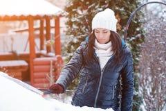 La mujer atractiva joven en ropa del invierno quita nieve del coche w Imagen de archivo