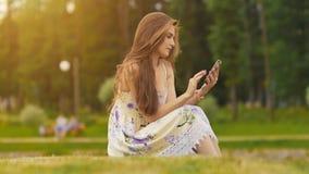 La mujer atractiva joven en vestido del verano se sienta en hierba verde con el teléfono móvil en manos E Verano reconstrucción Foto de archivo