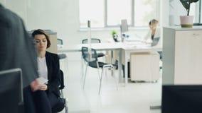 La mujer atractiva joven está esperando en la lectura de la oficina su curriculum vitae mientras que otro candidato está hablando almacen de video