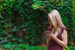 La mujer atractiva joven está mandando un SMS con su smartphone Fotografía de archivo