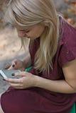 La mujer atractiva joven está mandando un SMS con su smartphone Foto de archivo libre de regalías