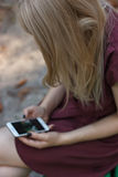La mujer atractiva joven está mandando un SMS con su smartphone Imagenes de archivo