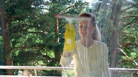 La mujer atractiva joven lava una ventana usando un cepillo especial Tiro del carro metrajes