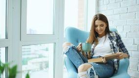 La mujer atractiva joven leyó el libro y bebe el café que se sentaba en balcón en el apartamento moderno del desván fotografía de archivo