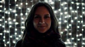 La mujer atractiva joven que goza de nieve que cae en la noche de la Navidad delante de la pared decorativa de chispear se encien Imagenes de archivo