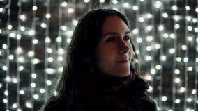 La mujer atractiva joven que goza de nieve que cae en la noche de la Navidad delante de la pared decorativa de chispear se encien Imagen de archivo libre de regalías
