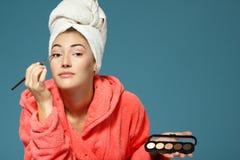 La mujer atractiva joven que pone la sombra de ojos con los cosméticos cepilla o Fotografía de archivo