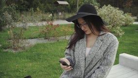La mujer atractiva joven se sienta en banco en el parque y trabaja en el smartphone almacen de video