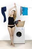 La mujer atractiva joven seca la ropa Fotos de archivo