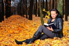 La mujer atractiva lee el libro Fotos de archivo