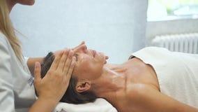 La mujer atractiva madura está disfrutando de su masaje de la cara almacen de video