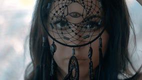 La mujer atractiva misteriosa con compone la mirada a través del colector ideal negro