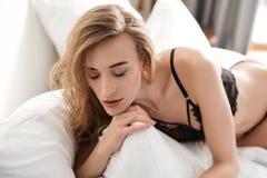 La mujer atractiva morena asombrosa miente en cama Fotografía de archivo