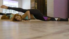 La mujer atractiva que hace estirar ejercita en el gimnasio almacen de video